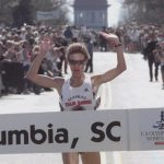 woman marathon runner raises arms as she wins the 2000 Olympic Marathon Trials